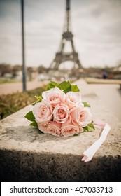 Pink rose wedding bouquet under the Eiffel Tower in Paris, France