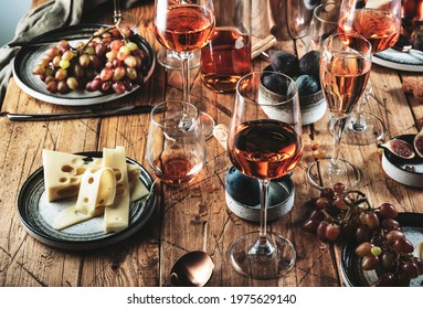 Pink rose wine glasses and bottles on table served for summer festive dinner party with different kinds of appetizers