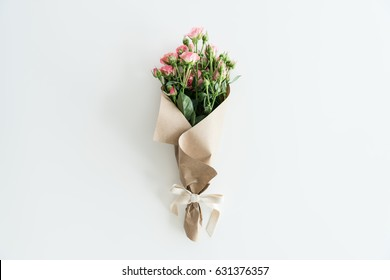 pink roses bouquet in kraft paper isolated on white with copy space, wedding flowers bouquet concept