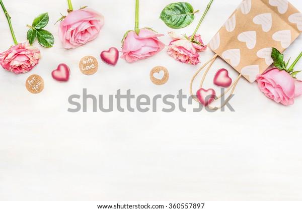 明るい背景にピンクのバラとチョコレートの心、買い物袋、丸いサインとメッセージ、明るい背景に愛のある、トップビュー。 バレンタインデーまたは誕生日のグリーティングカード。枠線