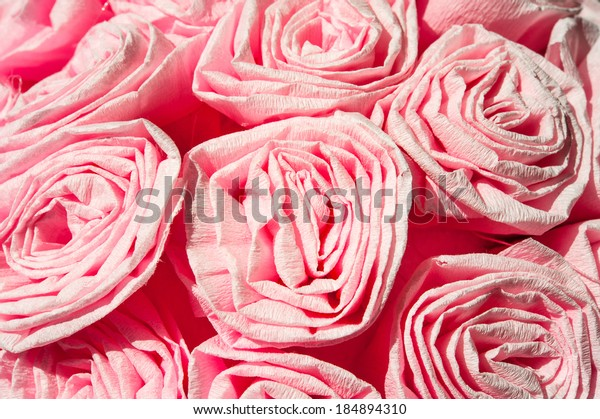 Pink roses from crepe paper. Celebrations decor. Closeup.