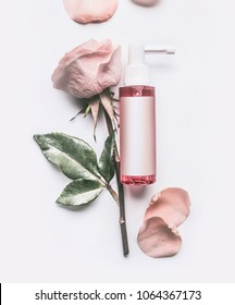 Pink Roses essential cosmetic product bottle with branding mock up and rose flowers and petals on white background, top view