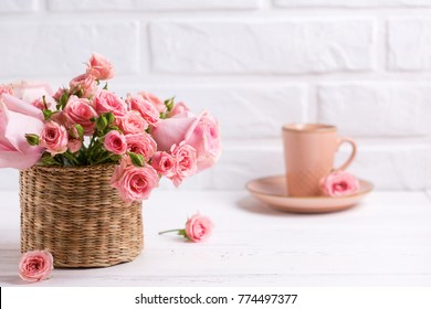 Pink roses flowers  and cup of coffee against  white brick wall. Floral still life.  Selective focus. Place for text.