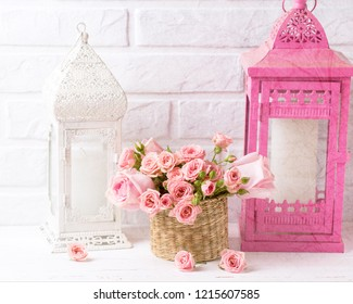 Pink roses flowers and decorative pink and white lanterns against  white brick wall. Floral still life. Toned image.  Selective focus.
