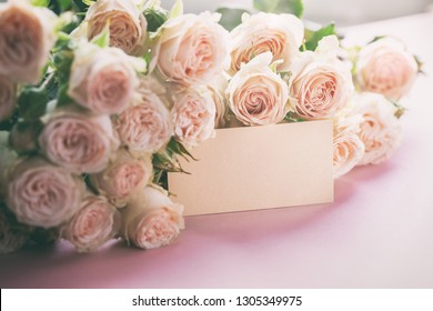 Pink roses flowers with gift card on pink background. Mothers Day, Birthday, Valentines Day, Womens Day, celebration concept. Space for text.