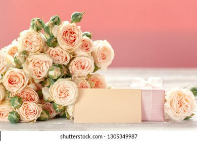 Pink roses flowers and gift or present box pink background. Mothers Day, Birthday, Valentines Day, Womens Day, celebration concept. Space for text.