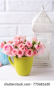 Pink roses flowers in green cup against  white brick wall. Floral still life.  Selective focus. Still life.