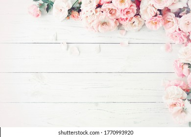 pink roses frame on white wooden background toned.Top view.Copy space. Poster