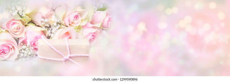 Pink roses and gift in front of pastel background