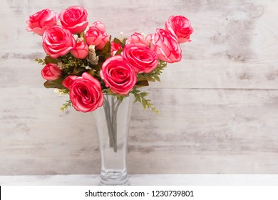 Pink roses in a glass on a light background Vintage