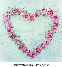 Pink roses in a hearth shape on vintage old wooden background