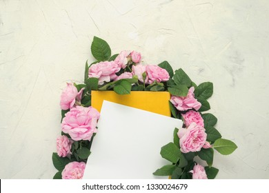 Pink roses are lined around a book with a yellow cover on a light stone background. The concept of books about love and romance novels. Flat lay, top view