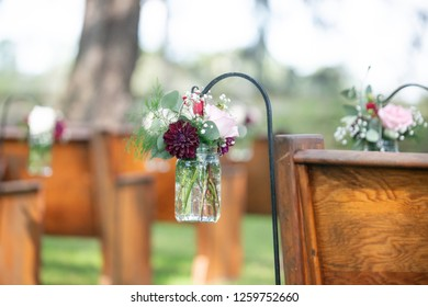 Pink roses in mason jars hanging on rows of wooden wedding ceremony pews