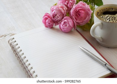 pink roses with notebook coffee cup and pen,  concept for mother's day, woman or birthday