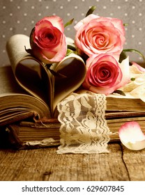 Pink roses and old books on wooden desk.