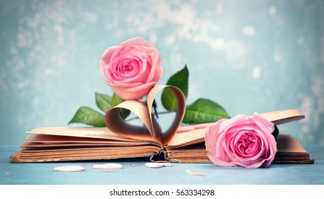 pink roses on an old book with heart in a vintage style
