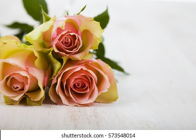 Pink roses on a wooden background. Greeting card with Valentine's Day, Birthday or Wedding.