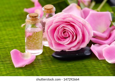 Pink roses with petals and massage oil with stone on green straw mat