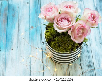 pink roses in striped gift box on blue wooden background with lights and copy space. top view. mothers day birhtday and holiday greeting card