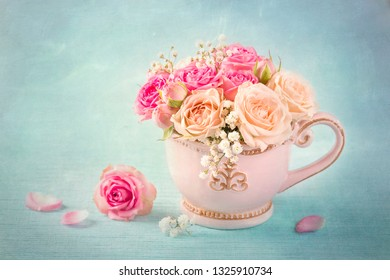 Pink roses in a teacup on a blue background