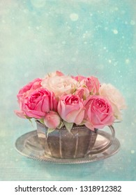 Pink roses in a teacup on a pastel blue background