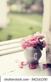 Pink roses in a vase in vintage style