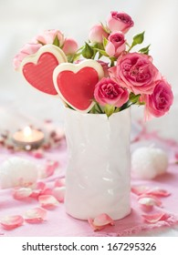 Pink roses in white cup with lollipop  for celebration, selective focus