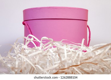 A pink round cardboard gift box is lined with paper shavings outside for packing buy on a white background close-up and with a ribbon in the form of a pen on the side.