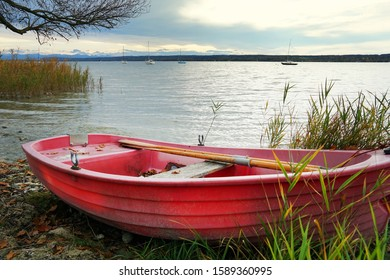 a pink rowboat on the shore of a Lake
