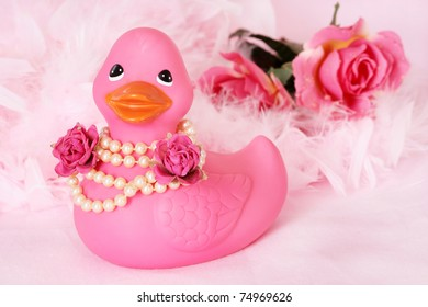 pink rubber duck with pearl necklace on, flowers and boa in the background on pink fabric.