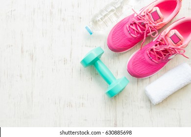 Pink running shoes with fitness accessories on white wooden background, Healthy concept