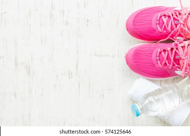 Pink running shoes with water and towel on white wooden background