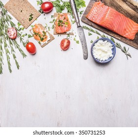 pink salmon fillet with tomatoes, rosemary, curd cheese, vintage cutlery and sandwiches border, place for text  on wooden rustic background top view