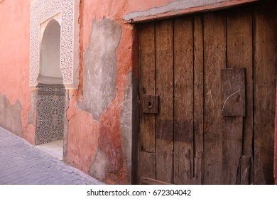 The pink sandstone walls of a building and rustic doorways in an alley in the fortified city of Marrakech, Morocco.