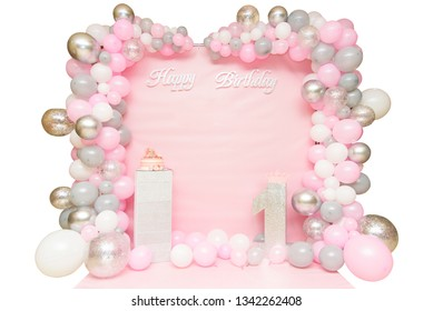 Pink Scenery To Celebrate Baby's First Year of Life. Photo zone with balloons, inscription happy birthday and cake.