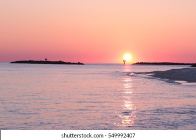 pink setting sun on horizon of gulf of mexico orange beach alabama