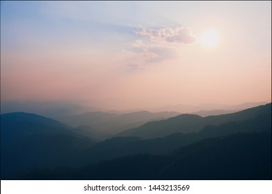 pink shades of sunset over the mountains. lines of mountains of different shades form a tonal perspective in pink and blue, Northern Thailand