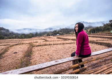 Pink shirt girl sitting in the field happily.