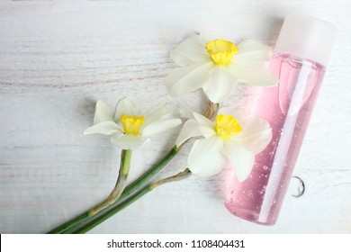 Pink shower gel and daffodils on a wooden background. Top view.