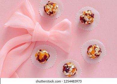 Pink silk bowknot and five healthy energy balls lying in circle on pink background.
