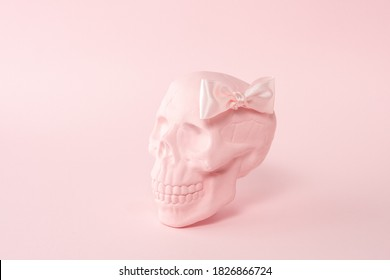 Pink skull with pink bow tie on a pink background. Minimal Halloween spooky girl concept.