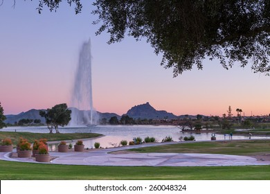 Pink sky behind one of the tallest fountains in the world in Fountain Hills, AZ with Fire Rock and Four Peaks in the background
