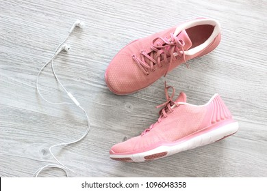 Pink sneakers on the wooden background