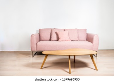 A pink sofa with metal frame and an oak coffee table in front of a white wall, over light hard wood floors.
