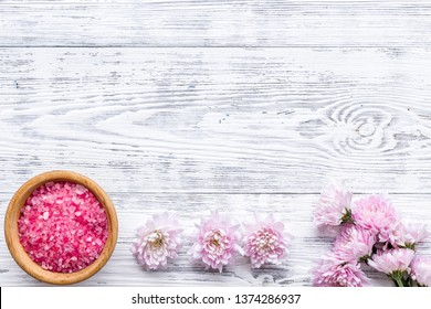 pink spa salt for aroma therapy with flower fragrance on white wooden background top view copyspace