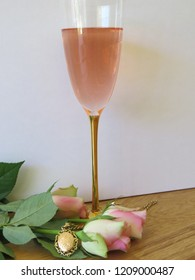 Pink sparkling with roses and a gold locket