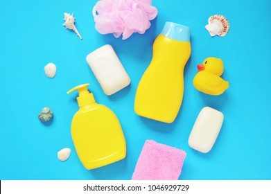Pink sponge, yellow shampoo bottle, liquid soap, towel, seashells and rubber duck on a blue background. Flat lay beauty products items