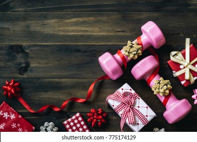 Pink sport dumbbells, gifts, and bows on wooden background, Merry christmas and Happy new year wish sport gifts greeting card concept top view with copy space