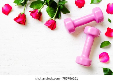 Pink sport dumbbells,  and red roses on white wooden background, Valentines sports background and greeting card any anniversary holiday background concept top view with copy space.