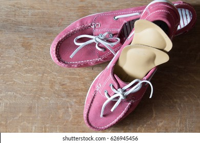 Pink sport shoes  with orthopedic insoles.  Pair of sneakers on wooden background